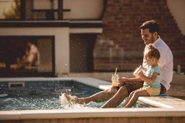Father and daughter funny time by the pool stock photo