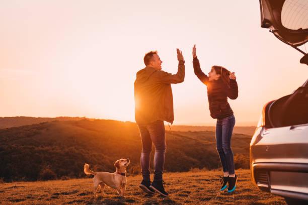 Vater und Tochter geben hohe fünf beim Springen während des Campings – Foto