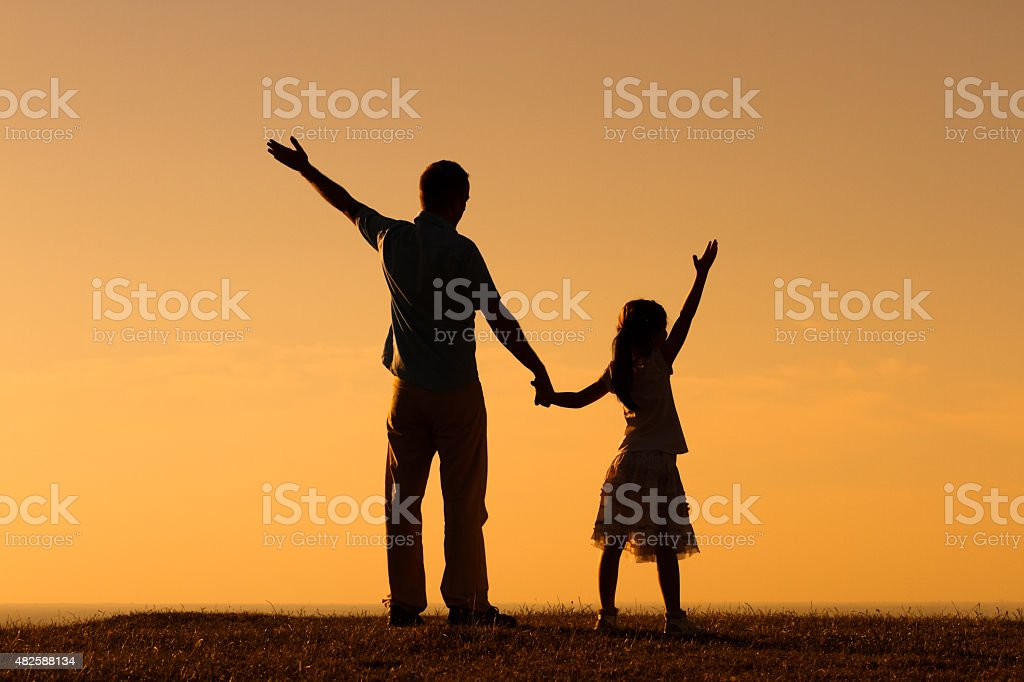 Father and daughter gretting the sunset stock photo