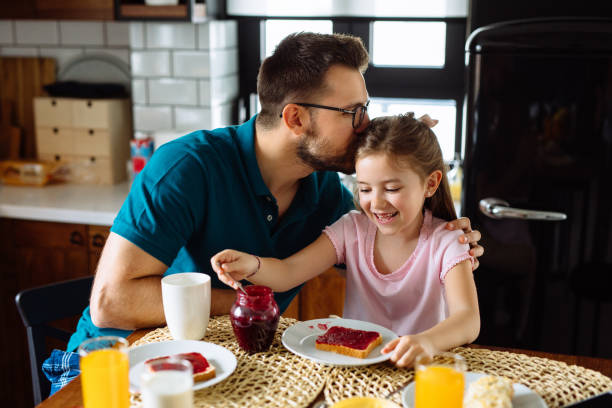 Father and daughter having breakfast at home stock photo