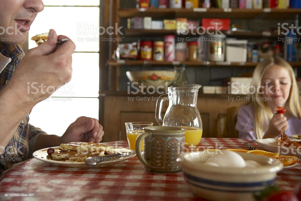 Father and daughter (10-11) having breakfast royalty-free stock photo
