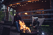 Father and daughter  having fun by the campfire at their cabin in the woods