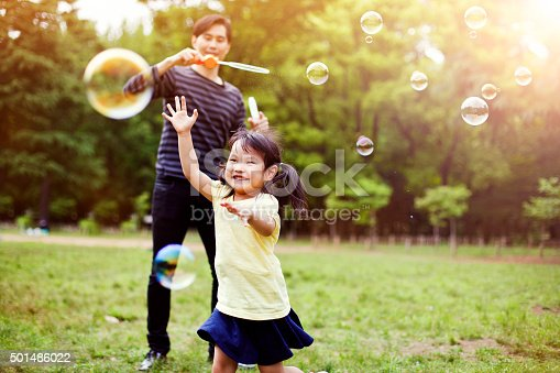 istock Father and daughter having fun in park with Soap Bubbles 501486022