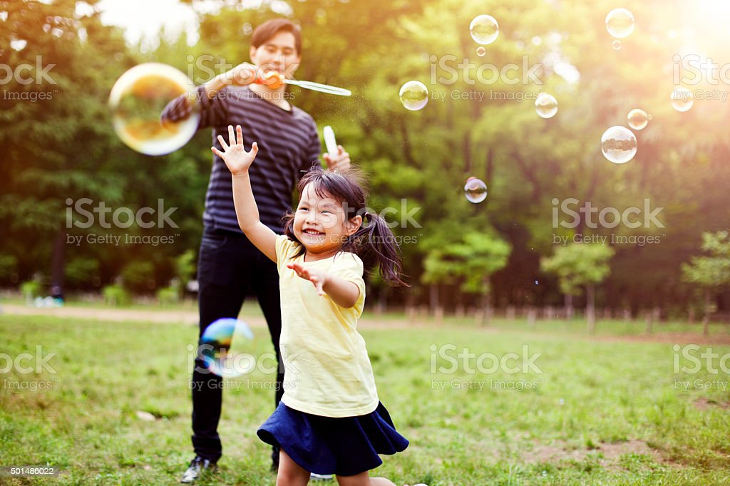 Father and daughter having fun in park with Soap Bubbles​​​ foto