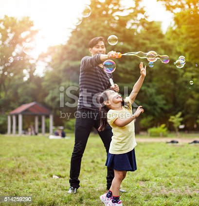 istock Father and daughter having fun in park with Soap Bubbles 514259290