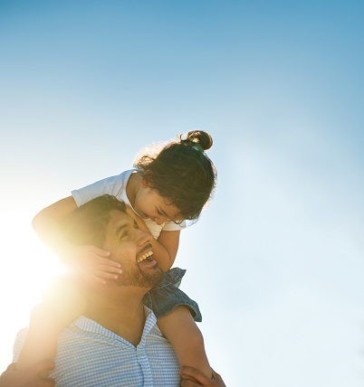 A young mixed race girl sits on her dad's shoulders, looking at each other, both smiling outdoors in the sun