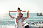 Father and daughter having fun on the beach. Playing together outdoors on a summer