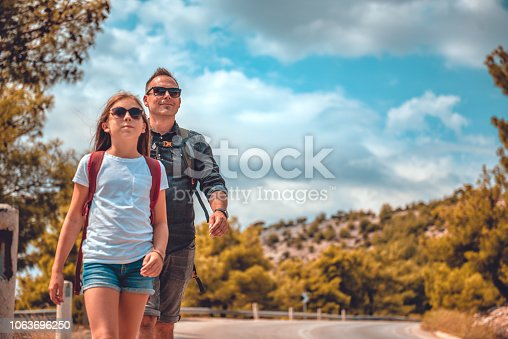 istock Father and daughter hiking on the mountain road 1063696250