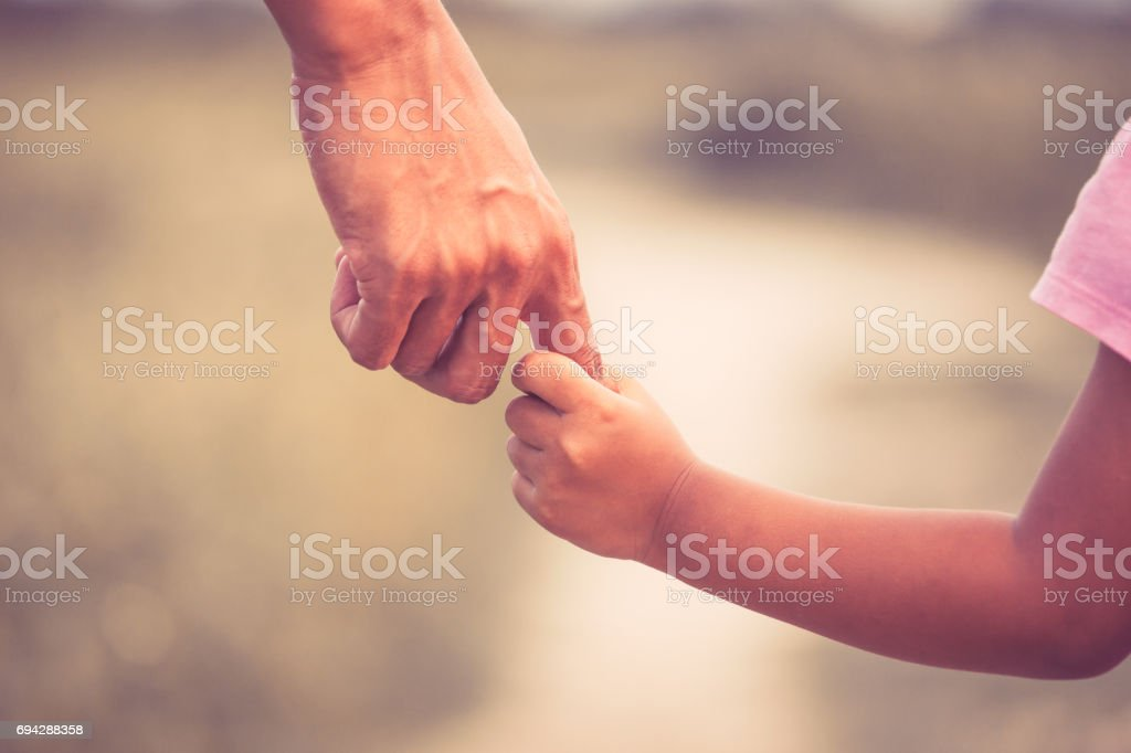Father and daughter holding hand together in vintage color tone stock photo