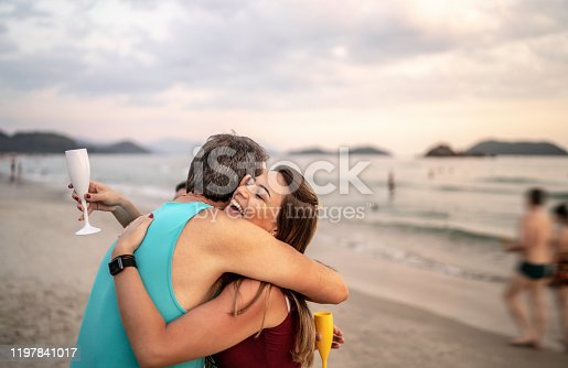 istock Father and daughter hugging on the beach celebrating New Year 1197841017