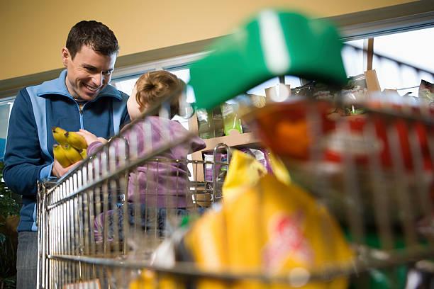 vater und tochter in einem supermarkt - hausmannskost stock-fotos und bilder