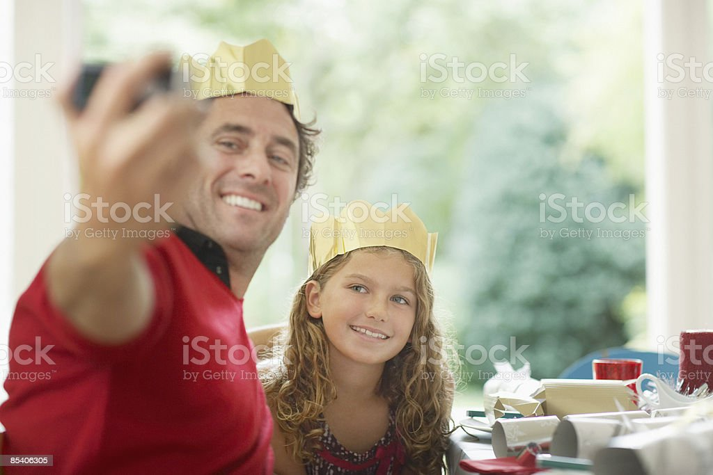 Father and daughter in Christmas crowns taking self-portrait stock photo