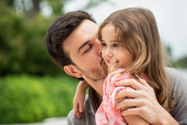 Father and daughter in domestic garden Close-up of father kissing daughter on cheek in domestic garden little girl kissing dad on cheek stock pictures, royalty-free photos & images