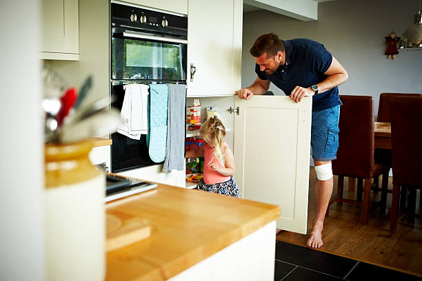 vater und tochter in der küche - hausmannskost stock-fotos und bilder