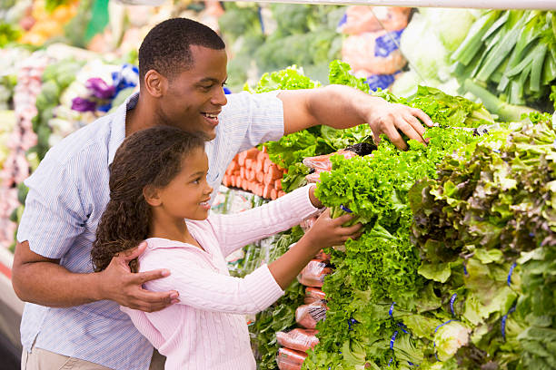 Father and daughter in produce section stock photo
