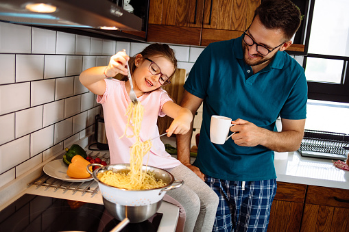 Father and daughter in the kitchen, eating spaghetti together