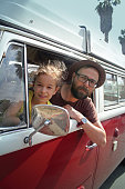 Father and daughter looking out of the window of a old red vintage campervan. Let the adventure begin!