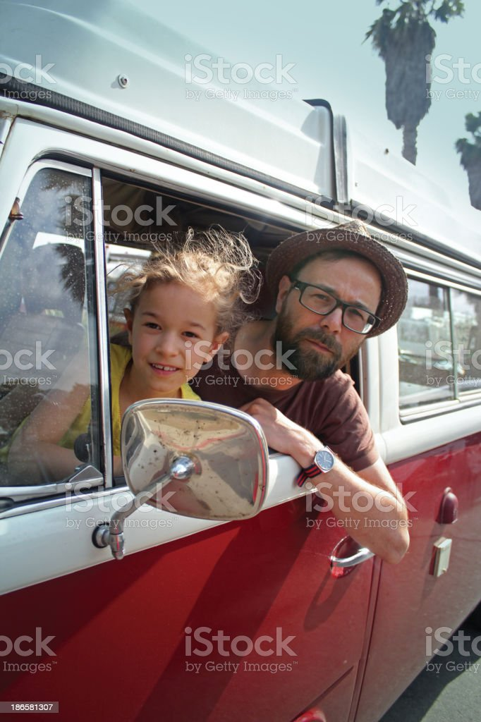 Father and daughter in vintage van on road trip stock photo
