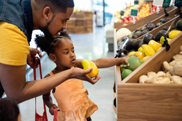 Father and daughter in zero waste oriented fruit and grocery store. stock photo