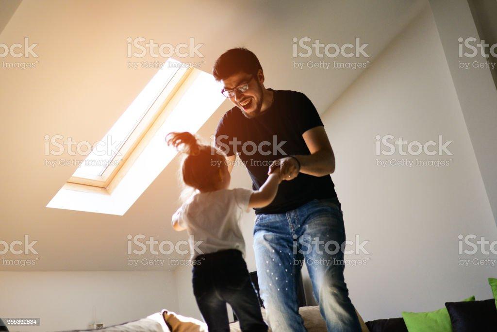 Vater und Tochter auf dem Bett zu springen und Spaß haben – Foto