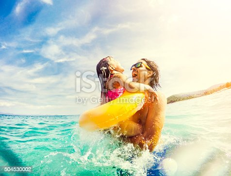 istock Father and daughter jumping and having fun together in sea 504530002