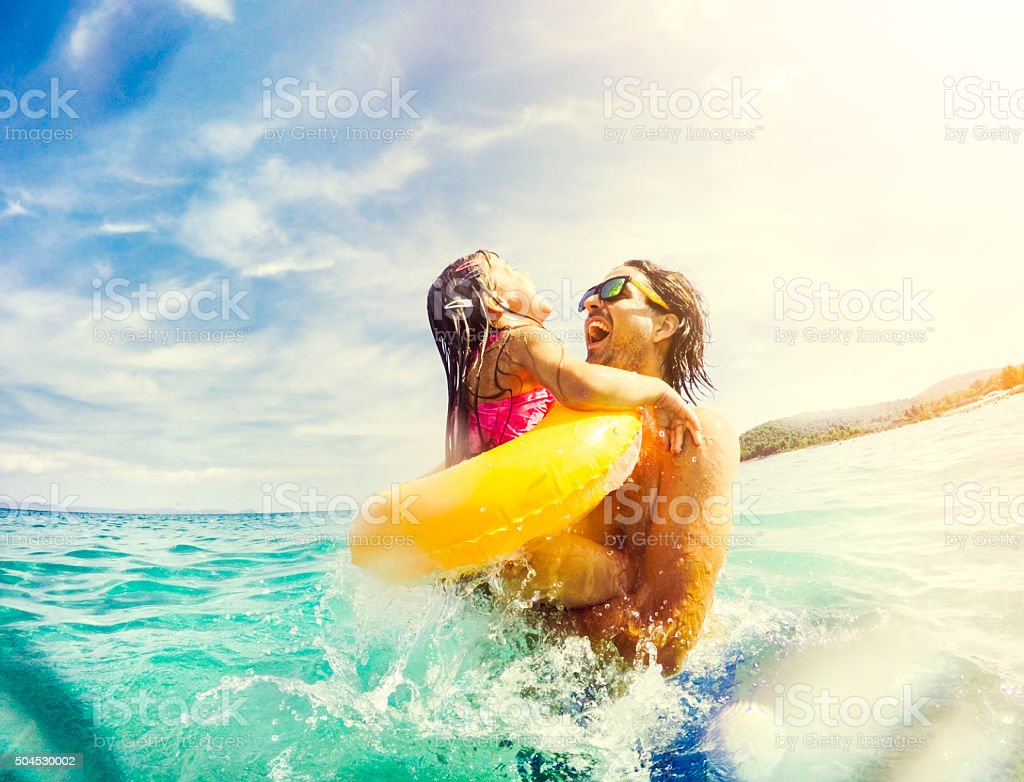 Father and daughter jumping and having fun together in sea stock photo
