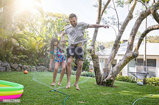 Father and daughter jumping in sprinkler at backyard garden.