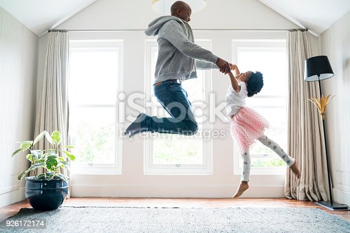 istock Father and daughter jumping while doing ballet 926172174