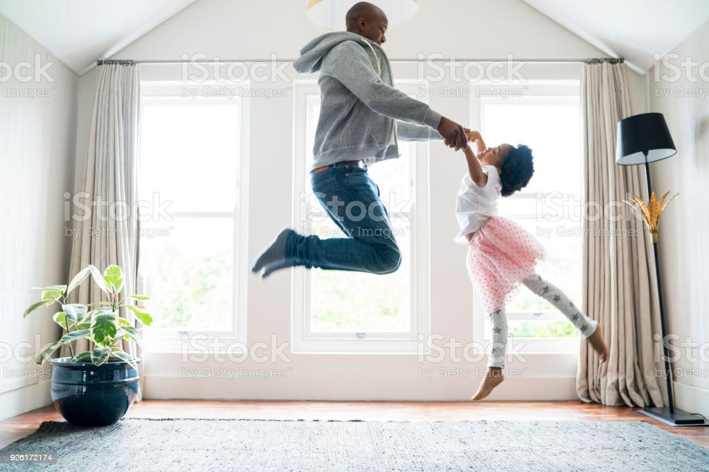 Father and daughter jumping while doing ballet stock photo