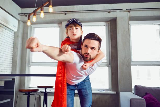 Vater und Tochter Kind in Anzügen Superhelden spielen im Zimmer. – Foto