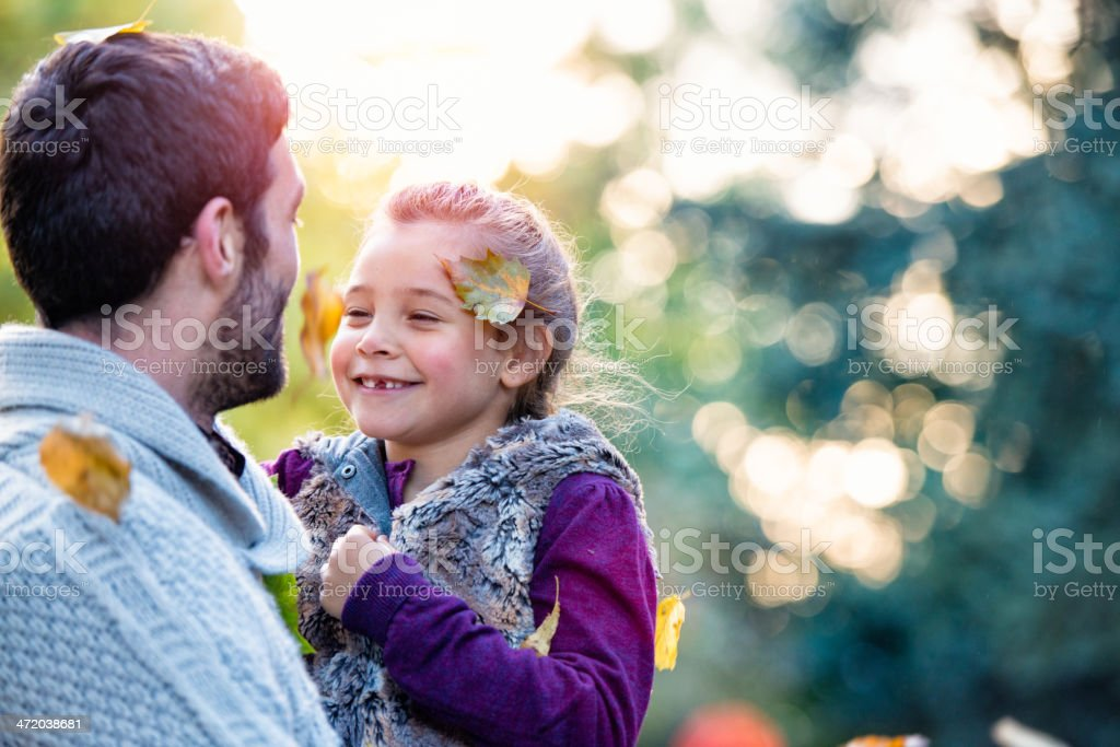 Father and daughter laughing in outdoor autumn setting stock photo