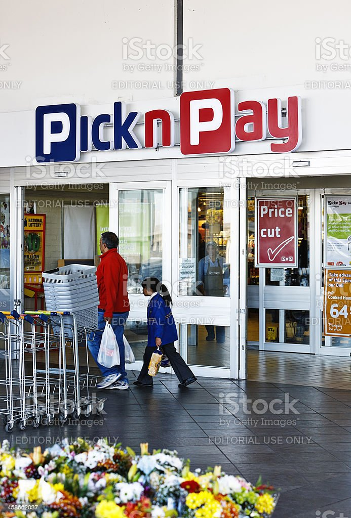 Father and daughter leave Pick n Pay supermarket with shopping stock photo