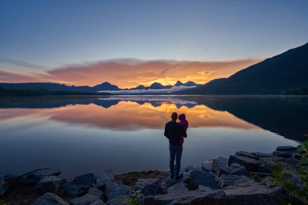 Father and Daughter Looking at a Vibrant Sunrise in the Beautiful Natural Scenery of Glacier National Park's Lake McDonald Area During the Summer in Montana, USA. stock photo