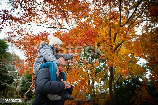 Father and daughter looking at autumn leaves with a shoulder car