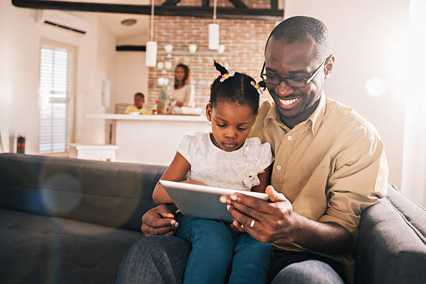 Father and daughter looking at digital tablet stock photo
