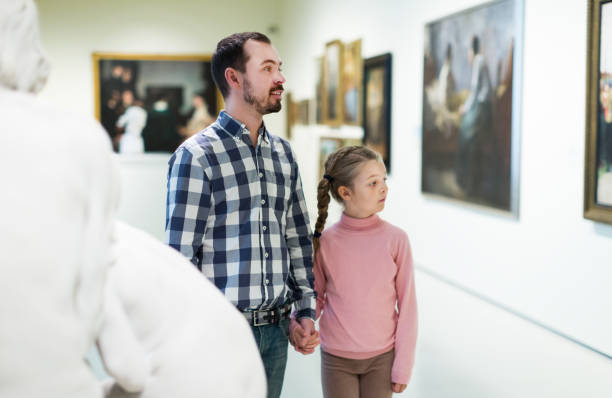father and daughter looking at expositions - museu imagens e fotografias de stock