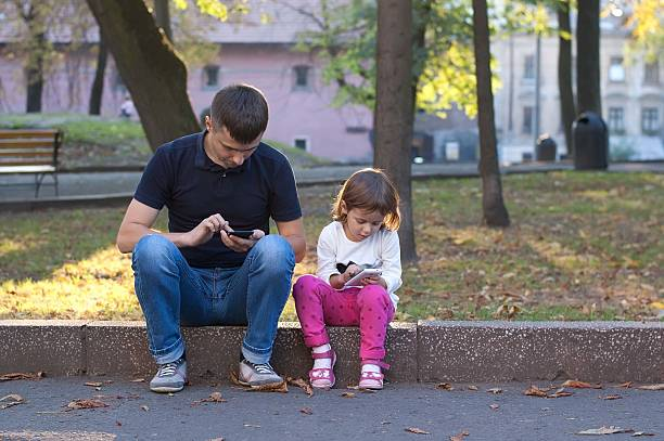 father and daughter looking at the phones while sitting outdoor. - free online game stock-fotos und bilder
