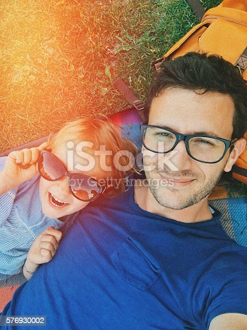 Father and daughter enjoying together on a picnic and lying on a grass