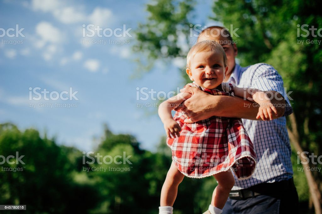 father and daughter. man and beautiful little girl outdoors in park stock photo