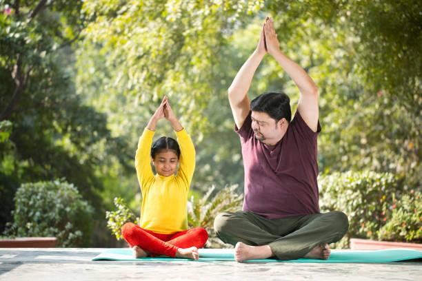 Vater und Tochter meditieren im Park – Foto