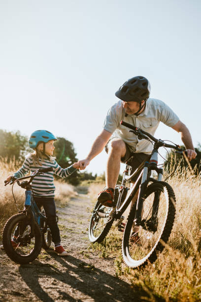Father and Daughter Mountain Bike Riding Together on Sunny Day