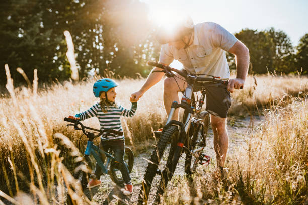 Father and Daughter Mountain Bike Riding Together on Sunny Day A dad mountain bikes together with his small daughter.  A fun way to spend time together and exercise while on vacation in the Seattle, Washington area. leisure equipment stock pictures, royalty-free photos & images