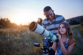 Father and daughter observing the sky with a telescope.
