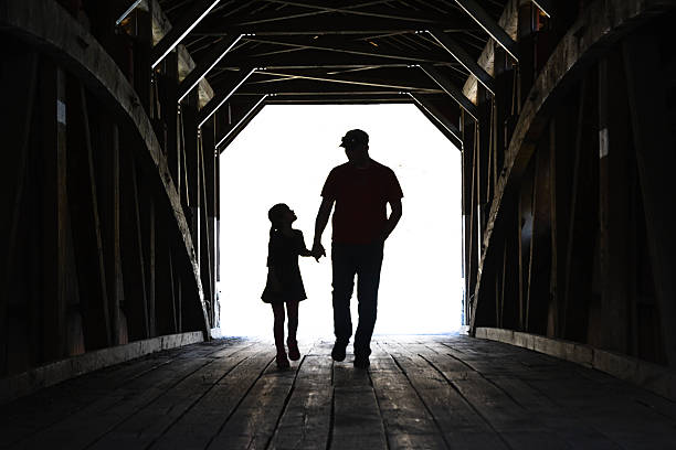 father and daughter on a covered bridge - fathers day stock photos and pictures