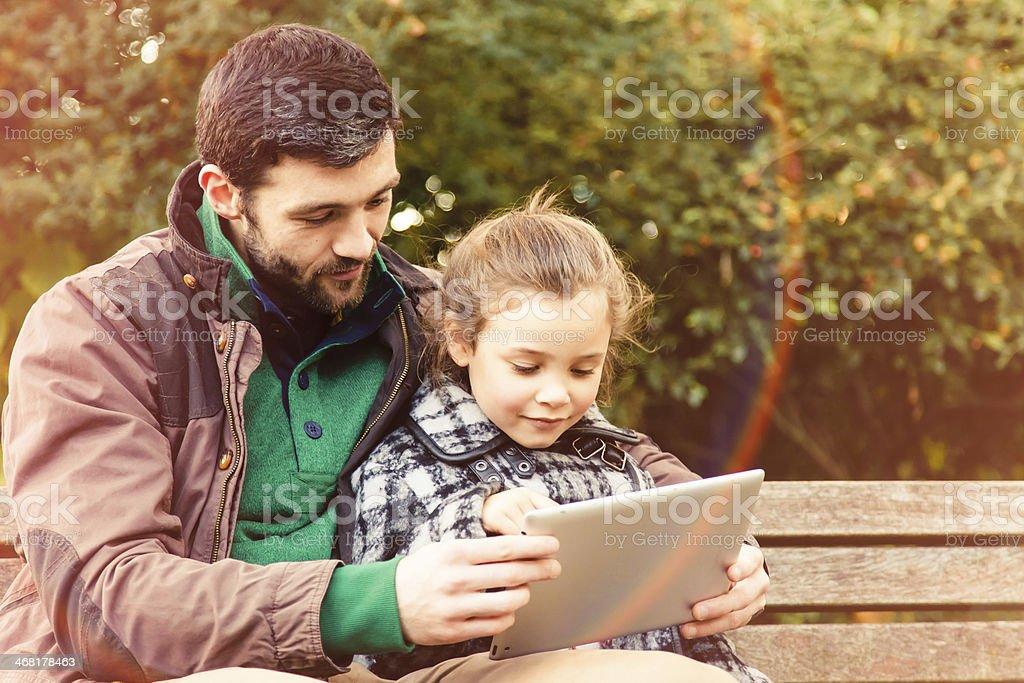 Ojciec i córka w parku z tabletką – zdjęcie