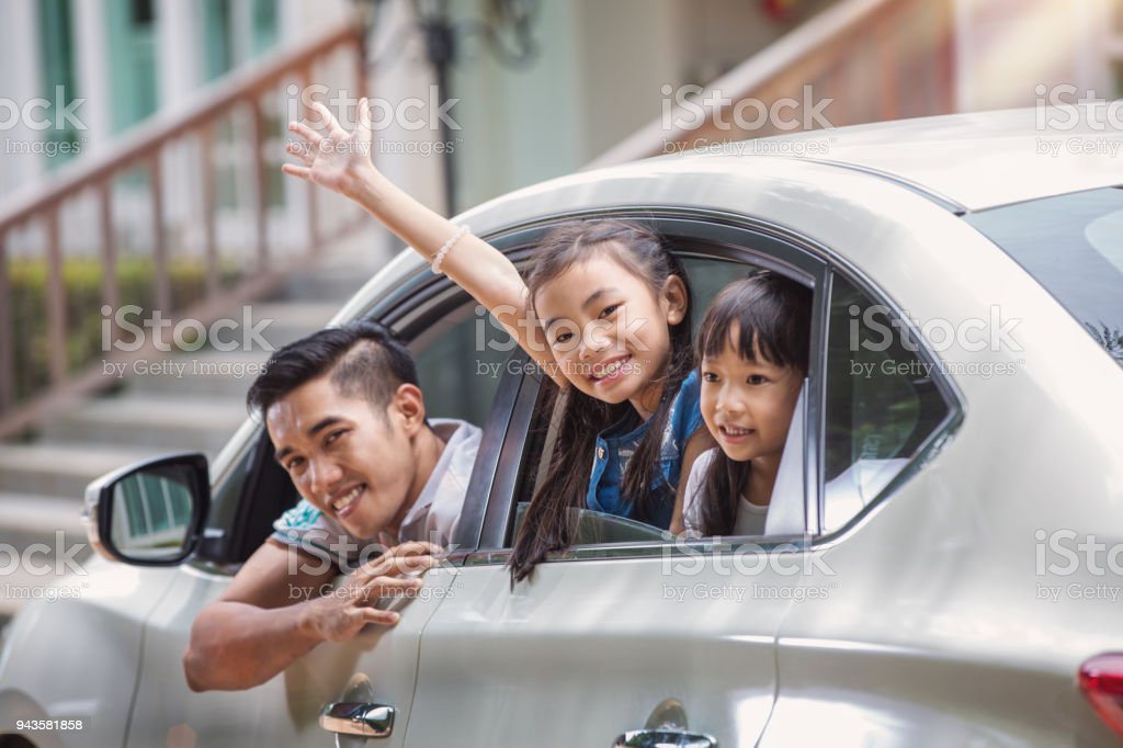 Father and daughter on car and smile from car windows stock photo