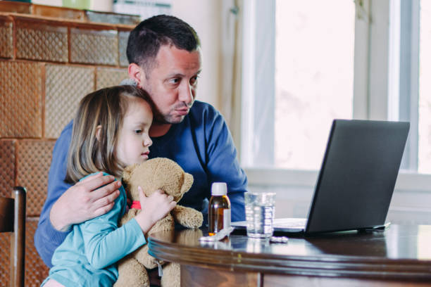 Father and daughter on telemedicine video call with doctor stock photo