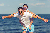 Young dad and his cute little daughter are spreading hands imitating flight and smiling. Girl is sitting on her father's shoulders, sunny sea in the background
