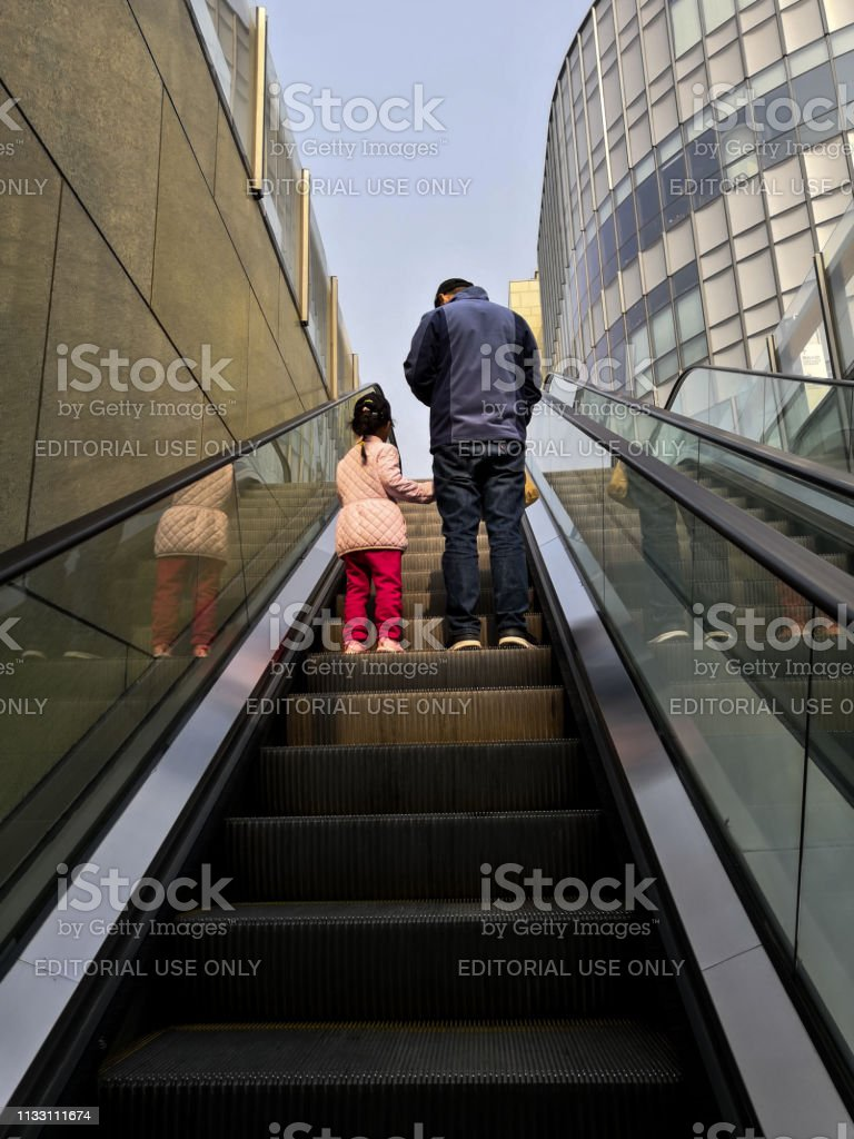 Father and daughter on the escalator in a shopping mall in Beijing, China stock photo