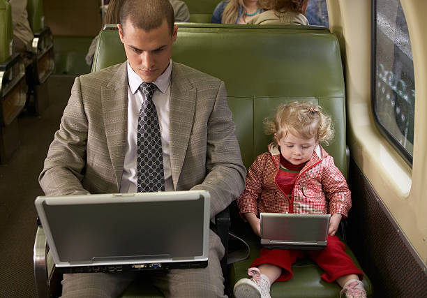 Father and daughter (1-3) on train using laptop and DVD player stock photo